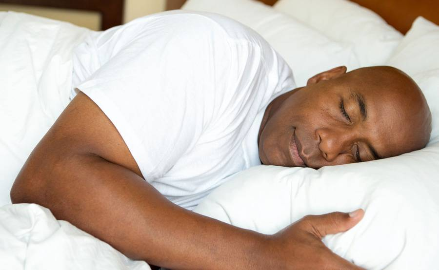 A man sleeping comfortably in bed represents how you can achieve a good night's rest with treatment from Scripps sleep medicine experts.