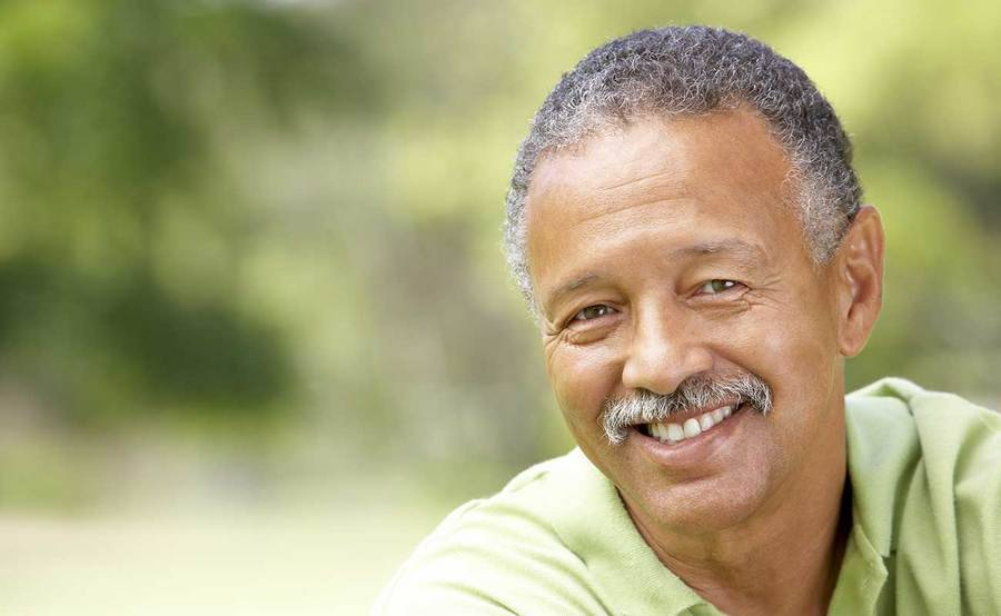 A smiling middle-aged African-American man represents the full life that can be led after soft tissue sarcoma treatment.