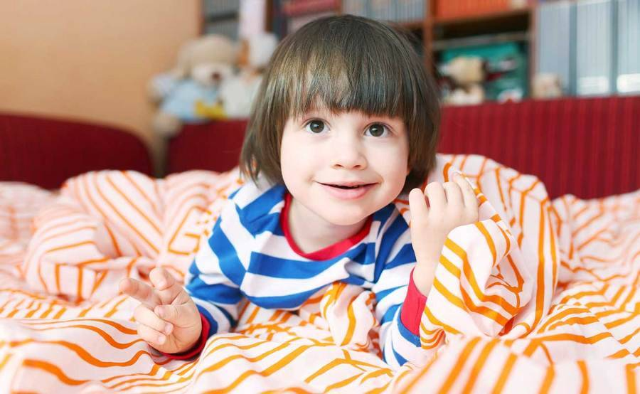Smiling child in striped pajamas gets ready for bed.