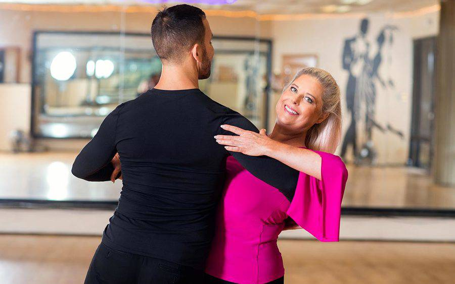 San Diego resident Suanne Summers practices ballroom dancing with a partner after spine surgery at Scripps.