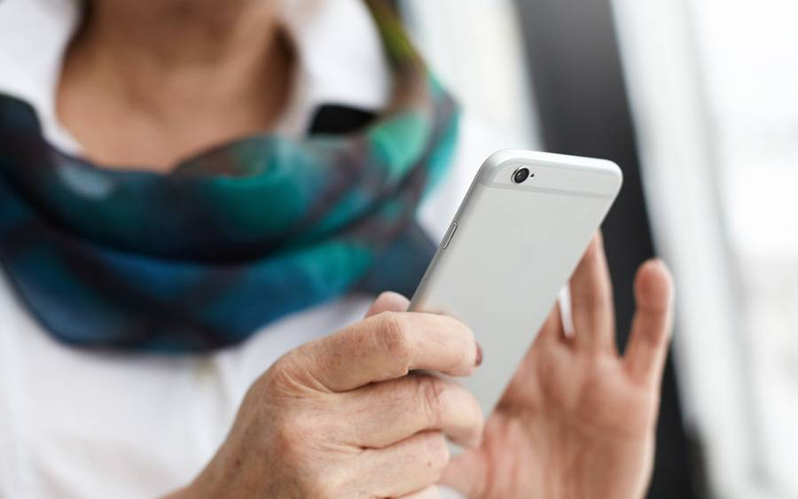 A middle age woman using her phone, represents the many Scripps patients that stay connected by following our social channels.