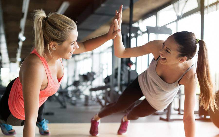 Two young women have fun while stretching and working out together.