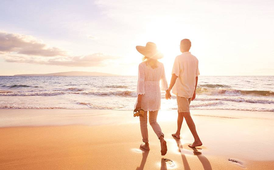 Couple holding hands and walking on the beach
