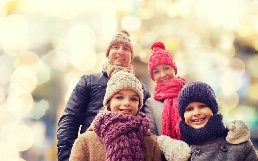 A family of four bundled up in scarves and knit caps enjoys a happy moment with blurred holiday lights in the background.