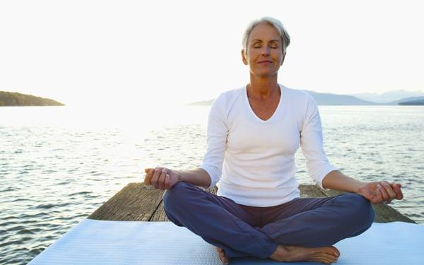 A woman meditates on a dock, similar to the practices taught during the mindfulness-based stress reduction course at Scripps Center for Integrative Medicine in San Diego