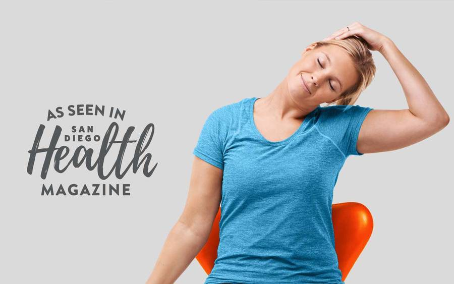 A young Caucasian woman tilts her head toward her left shoulder, demonstrating the easy stretches to prevent chronic neck and back pain.
