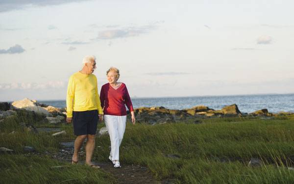 Joint replacement information class image of couple walking near ocean
