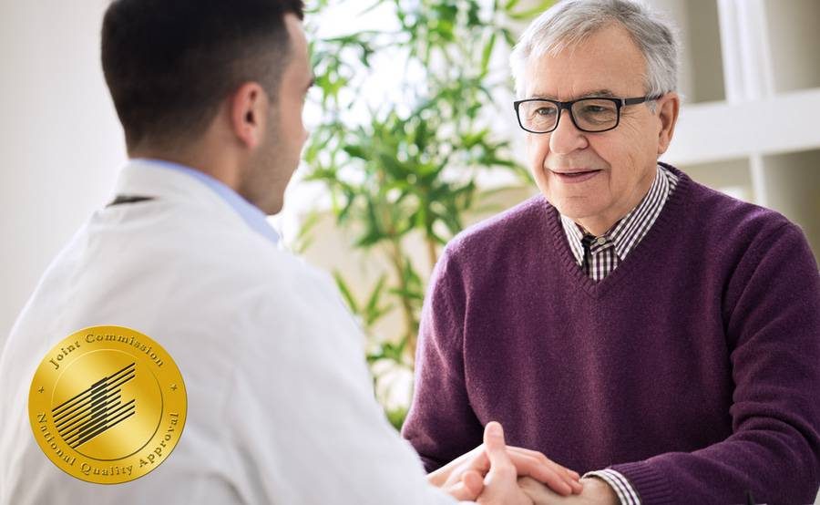 A smiling mature man talks with his doctor while holding hands, representing the expert stroke care at Scripps.