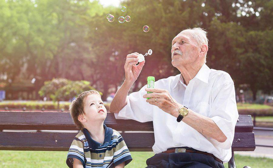 A mature man blows bubbles with his grandson on a park bench, representing the importance of stroke prevention.