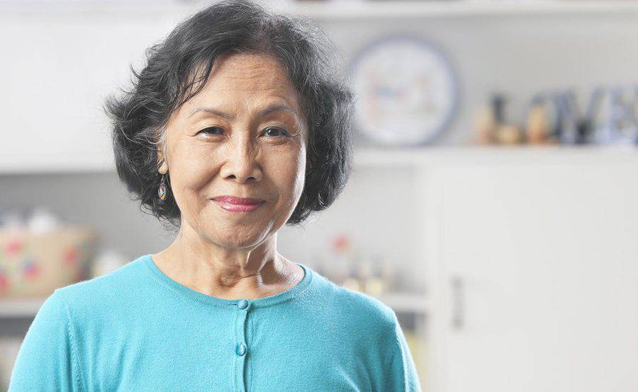 A smiling mature woman in her kitchen represents the importance of knowing the signs and symptoms of stroke.