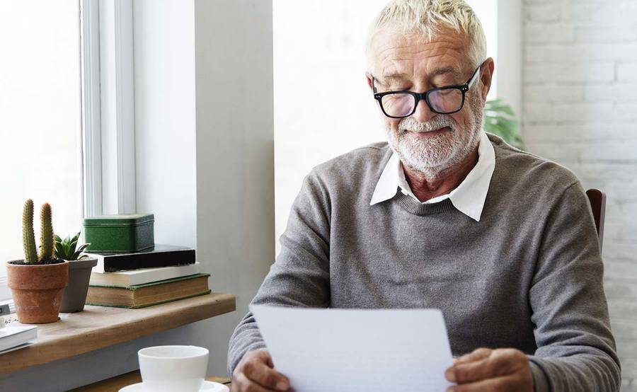 A smiling mature man reads paperwork over a cup of coffee, representing the improved quality of life that can be gained from quick treatment for stroke.