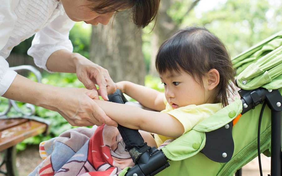 A mother bends over her child in a stroller to examine a bee sting in an outdoor environment.