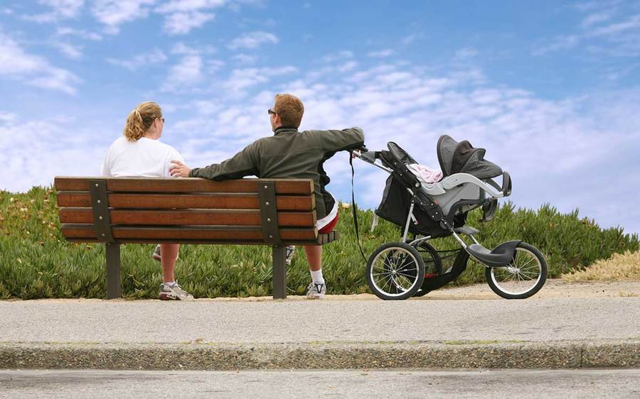 Two parents relax in the sunshine on a park bench while their baby stays safe in a covered stroller.