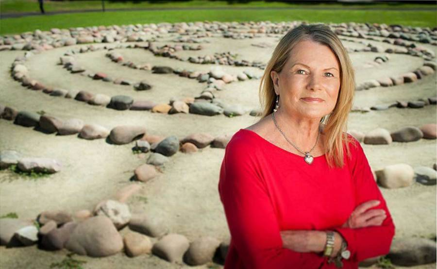Portrait of heart patient and advocate Susan Iliff with meditation labyrinth in the background.