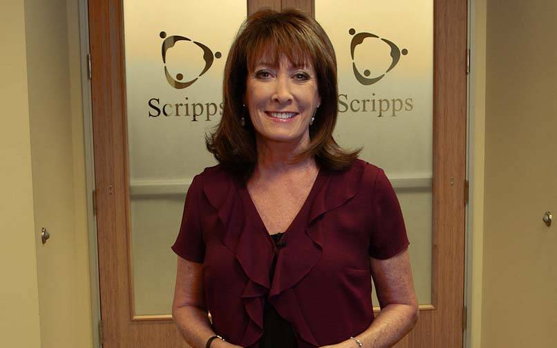 A smiling Susan Taylor portrait standing before two doors embossed with Scripps logo.