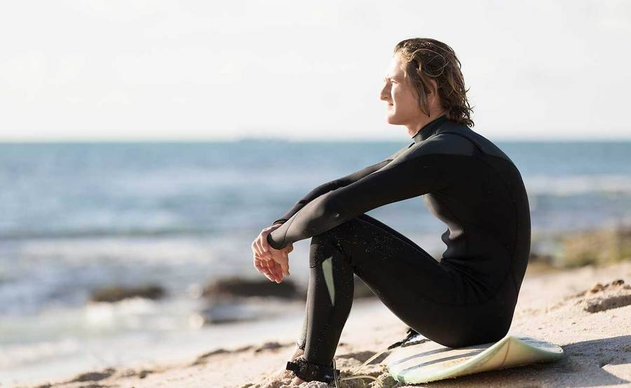A young surfer sitting on the beach represents the full life that can be led after testicular cancer treatment.