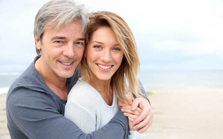 A happy middle aged man and woman embrace on a beach.