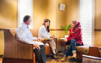 Woman consulting with two doctors about genetic testing for breast cancer risk.