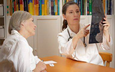 A female doctor explains the results of a CT scan with a stroke patient.