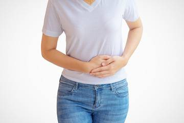 A woman with constipation is holding her tummy, hoping for constipation relief.
