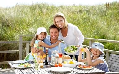 A family on vacation eats a healthy meal with plenty of green vegetables.