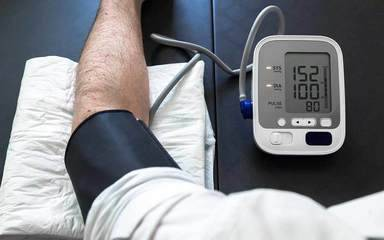 A man monitors his blood pressure at home, representing the importance of keeping track of hypertension.