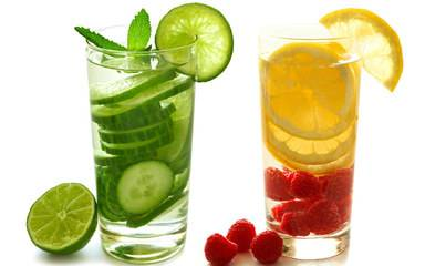 A glass of water with cucumber slices and a glass of water with lemon and raspberry represent the easy ways to enjoy flavored water to help prevent dehydration.