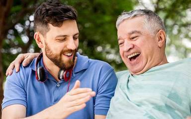 Two generations of men laugh and high five, representing the good life that can be led after prostate cancer surgery with the right help.