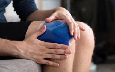A man presses an ice pack on his bruised knee; how to treat bruises is the featured topic in this Scripps article.