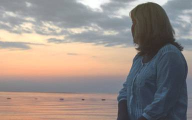 A woman contemplates menopause during sunset at the beach.