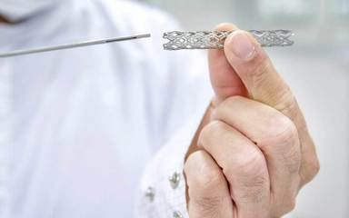 A doctor wearing a lab coat holds a heart stent