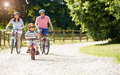 A family enjoys a bike ride together on a sunny day.