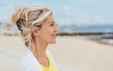 A woman at the beach looking pensive after recovering from minimally invasive robotic surgery for a gynecological condition.