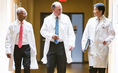 Scripps MD Anderson medical director Thomas Buchholz, MD, walks with two radiation oncologists, representing a powerful partnership in San Diego cancer treatment.
