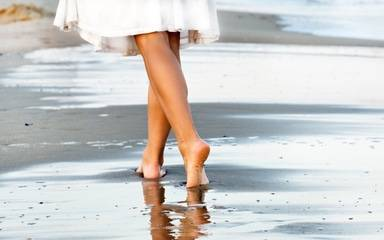 A woman walks on the beach is featured in a photo for a story about varicose vein prevention and treatment.