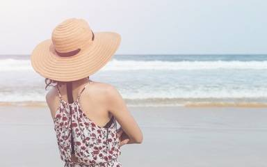 A woman wears a wide-brimmed at hat the beach to protect herself against developing skin cancer.