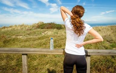 A woman wearing athletic apparel stretches to help relieve back pain.