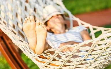 A young Caucasian woman in a hammock represents how a sedentary lifestyle can end up hurting your health.