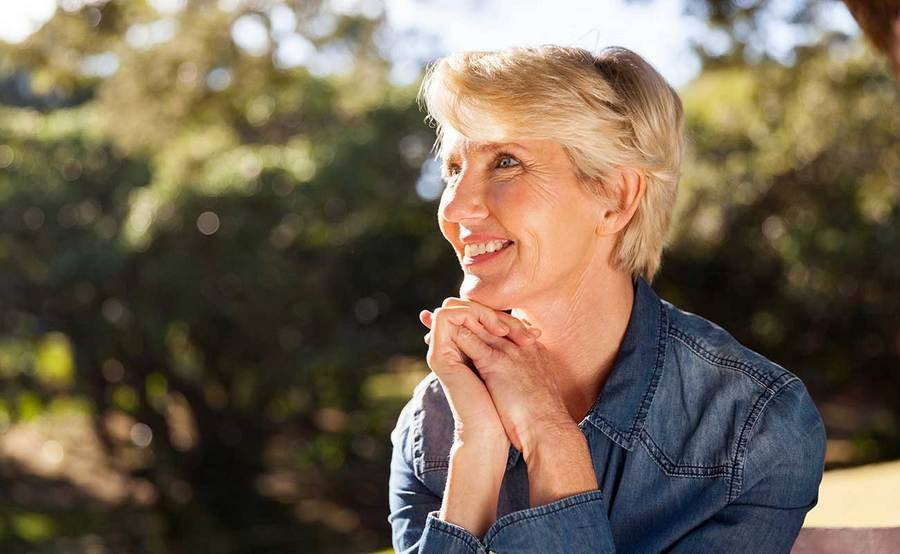 A smiling middle-aged woman represents the full life that can be led after thyroid cancer treatment.