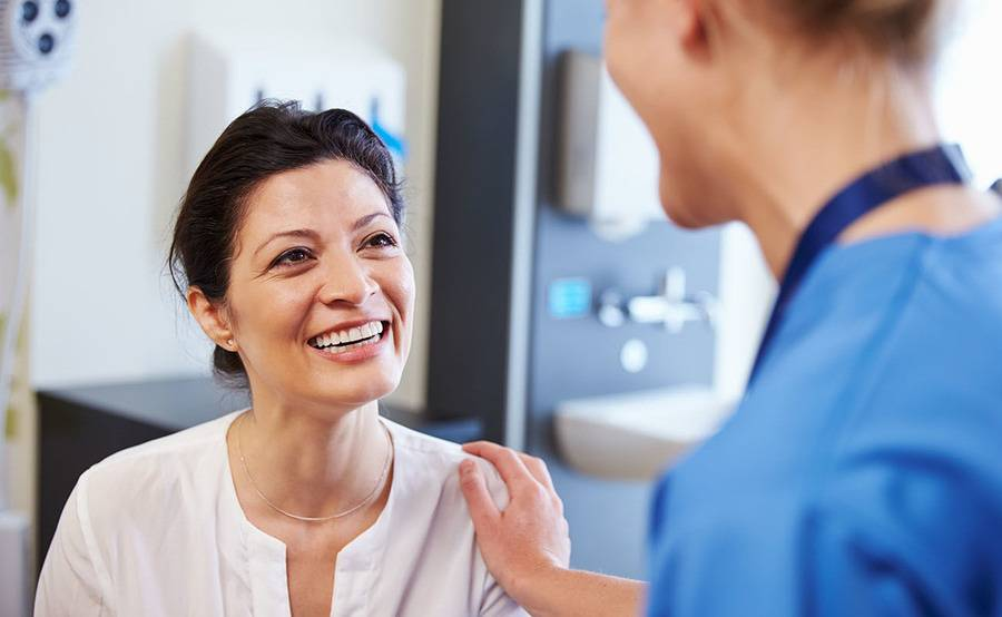A smiling middle-aged woman talks to her doctor, representing the expert and compassionate thyroid disease treatment at Scripps.