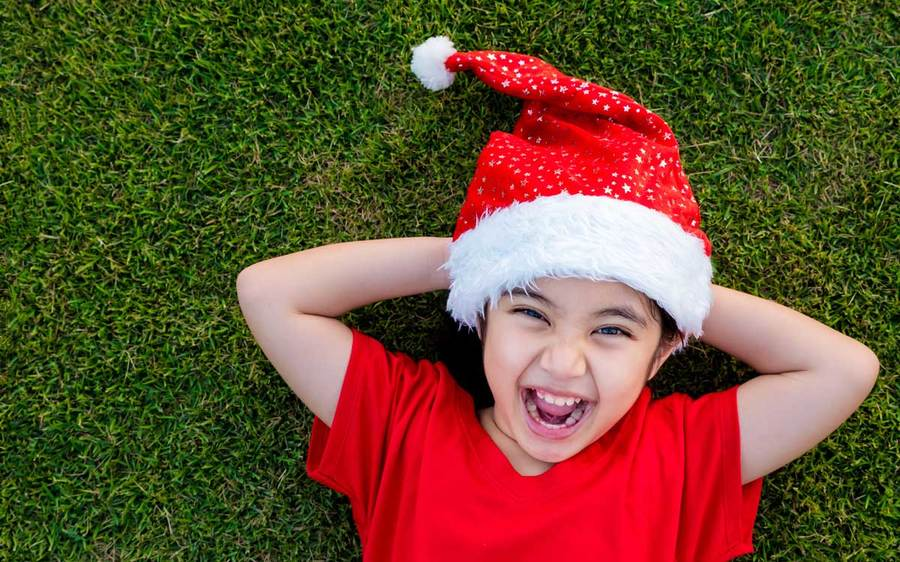 A laughing child in a red shirt and Santa hat lies on a grassy lawn with his hands behind his head