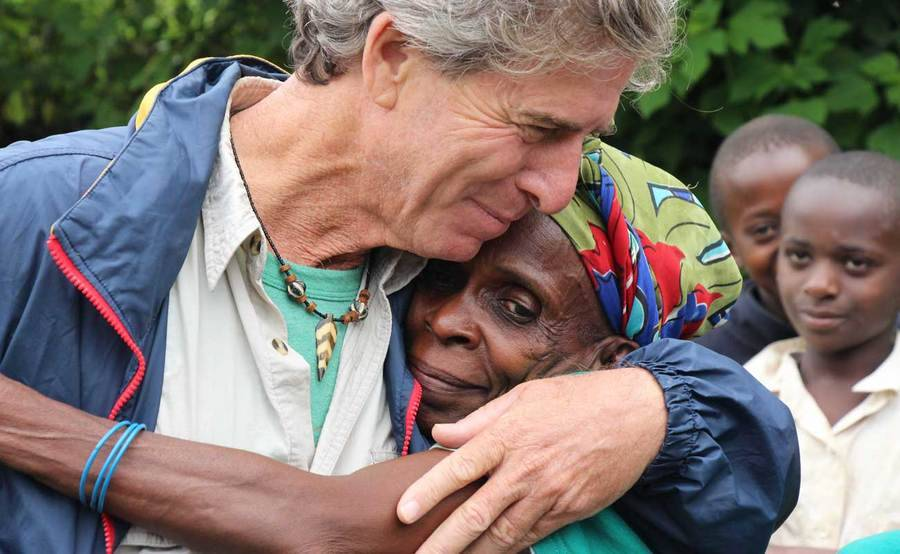 Biologist Bill Toone hugs a woman in Africa.