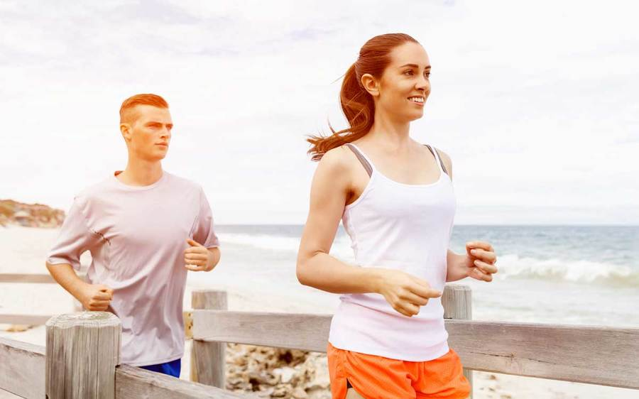An athletic man and woman run along the beach in preparation for an upcoming 5K race.