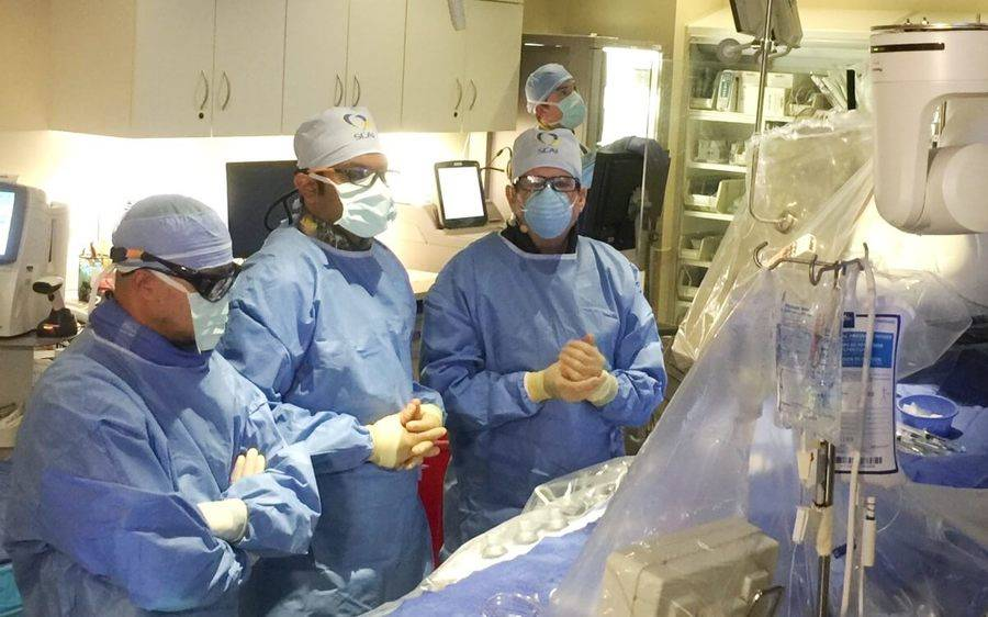 A team of doctors in an operating room as they prepare to begin a heart procedure that will be done through the wrist.