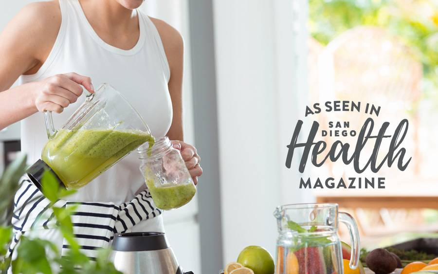 A woman pours a green smoothie from a blender into a mason jar, representing unhealthy eating habits.