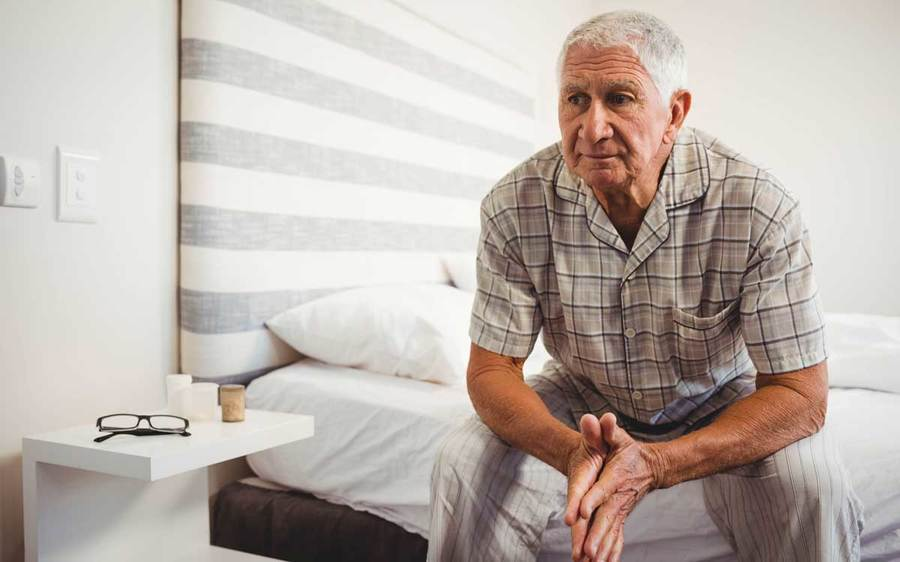 A thoughtful elderly man sits on his bed near a nightstand holding his glasses and candles.