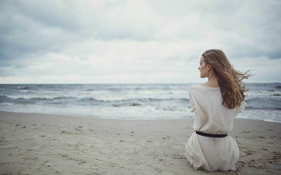 A woman sits on the beach in a white dress looking thoughtful and sad.