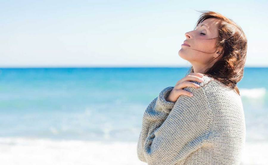 A calm middle-aged woman at the beach represents the full life that can be led after urethral cancer treatment.