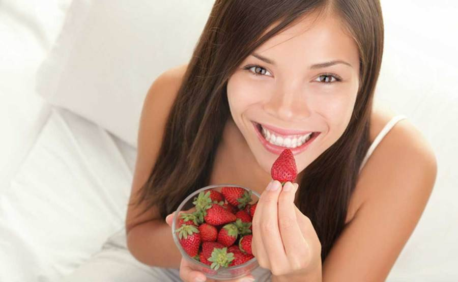 A happy woman prepares to bite into a heart-healthy strawberry.