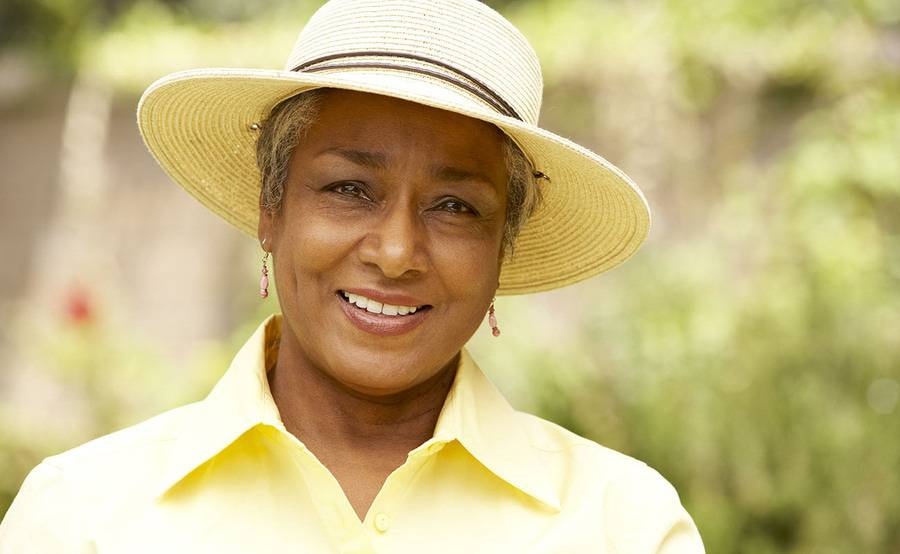 A smiling middle-aged woman in a sun hat represents a fuller life with treatment or surgery for vascular disease.